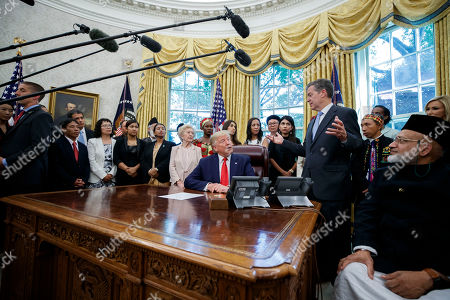 Donald Trump, Sam Brownback. President Donald Trump listens to Ambassador-at-Large for International Religious Freedom Sam Brownback, standing right center, as he meets with survivors of religious persecution in the Oval Office of the White House, in Washington. The survivors come from countries including, Myanmar, New Zealand, Yemen, China, Cuba, Eritrea, Nigeria, Turkey, Vietnam, Sudan, Iraq, Afghanistan, North Korea, Sri Lanka, Pakistan, Iran and Germany
