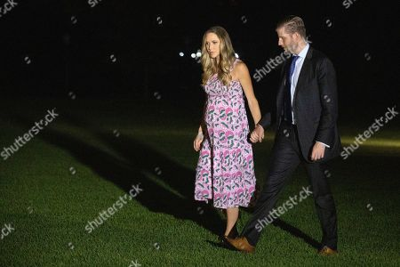 Eric Trump and his wife Lara Trump walk as they arrive with President Donald Trump on Marine One on the South Lawn of the White House in Washington, as he returns from a campaign rally in North Carolina