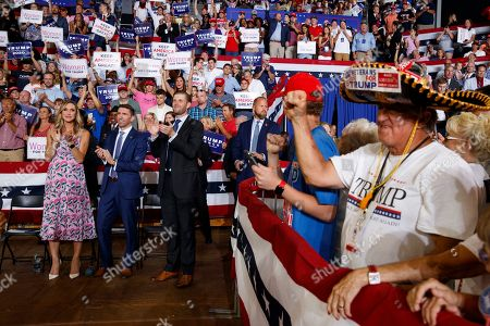 Eric Trump, the son of President Donald Trump, and his wife Lara Trump and her brother Kyle Yunaska, applaud during a campaign rally at Williams Arena in Greenville, N.C