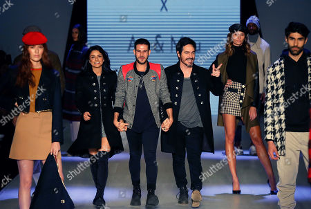 Mexican designer Jaime Kohen (C) along with Mexican actors Aislinn Derbez (L) and Mauricio Ochmann (R) walk the catwalk during Kohen's show at the 71st edition of Intermoda in Guadalajara, Jalisco state, Mexico, 17 July 2019.