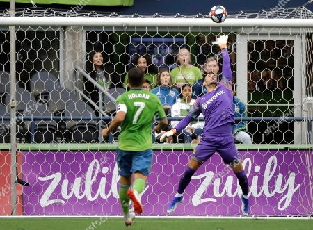 Borussia Dortmund goalkeeper Roman Burki, right, leaps as a shot hits the crossbar and Seattle Sounders midfielder Cristian Roldan (7) watches during the first half of an exhibition soccer match, in Seattle