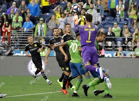 Borussia Dortmund goalkeeper Roman Burki (1) leaps for the ball during the second half of the team's friendly soccer match against the Seattle Sounders, in Seattle. Dortmund won 3-1
