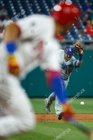 Cesar Hernandez, Max Muncy. Los Angeles Dodgers third baseman Max Muncy, right, commits a fielding error allowing Philadelphia Phillies' Cesar Hernandez, left, to reach first base during the sixth inning of a rain-delayed baseball game, early Thursday morning, in Philadelphia. Los Angeles won 7-2