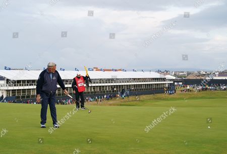 Darren Clarke sinks a birdie putt on the 1st hole during Round 1 of the 148th Open Championship.