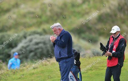Darren Clarke of Northern Ireland walks around the course