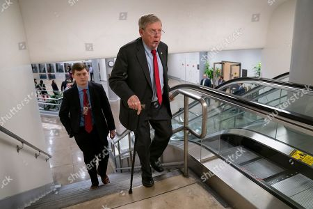 From, Sen. Johnny Isakson, R-Ga., climbs the stairs as he arrives at the Capitol for the vote to confirm William Barr's nomination to become attorney general, in Washington, Thursday, Feb. 14, 2019. The 74-year-old lawmaker has been hospitalized after he fell and fractured four ribs in his Washington apartment Tuesday night. The Republican has been a senator since 2005