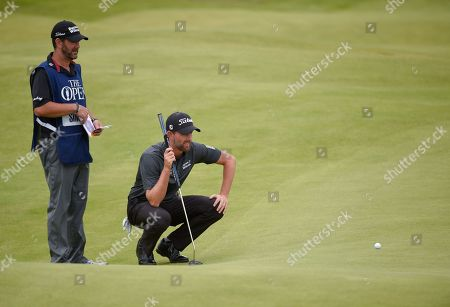 Stock Image of Webb Simpson of USA lines up a putt alongside his caddie Paul Tesori on the second green