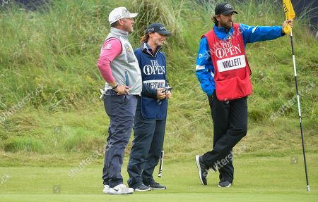 Lee Westwood and his girlfriend and caddie talk to the caddie of Danny Willett on the 18th green