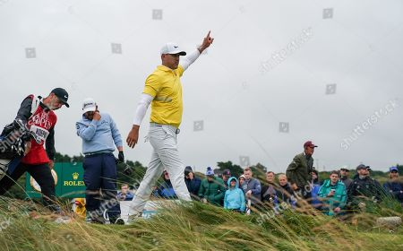 Brooks Koepka signals to a Marshall after JB Holmes sent his tee shot into the rough on the left of the 12th hole