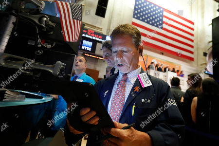 Trader Robert Charmak works on the floor of the New York Stock Exchange, . U.S. stocks moved lower in early trading on Wall Street Thursday after Netflix reported a slump in new subscribers and dragged down communications companies