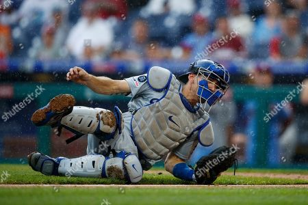 Los Angeles Dodgers' Austin Barnes dives for a throw during a baseball game against the Philadelphia Phillies, in Philadelphia