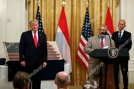 Stock Picture of Lonnie Bunch, Donald Trump, Bert Kreuk. Lonnie Bunch, the new Secretary of the Smithsonian, joined by President Donald Trump, left, and Dutch collector Bert Kreuk, right, speaks during a ceremony in the East Room of the White House, in Washington. The 48-star flag flown on a U.S. Naval vessel during the D-Day invasion during was presented during the ceremony. The flag will be given to the Smithsonian's National Museum of American History. The vessel was control vessel Landing Craft, Control 60 (LCC 60