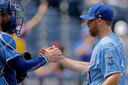 Kansas City Royals catcher Cam Gallagher, left, and relief pitcher Ian Kennedy celebrate after their baseball game against the Chicago White Sox, in Kansas City, Mo