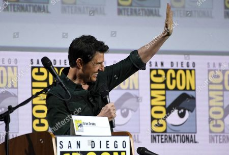 "Tom Cruise waves to the audience after presenting a clip from ""Top Gun: Maverick"" on day one of Comic-Con International, in San Diego"