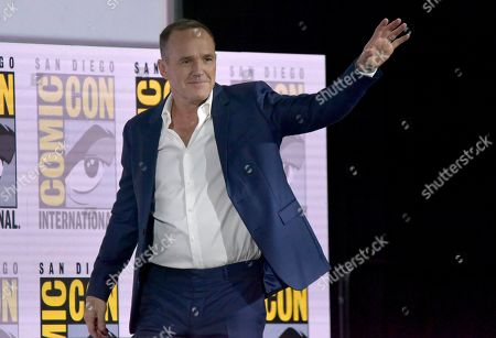 """Clark Gregg waves to the audience as he walks on stage at the """"Agents of S.H.I.E.L.D."""" panel on day one of Comic-Con International, in San Diego"""