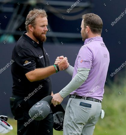 Shane Lowry of Ireland shakes hands with Branden Grace of South Africa on the 18th green