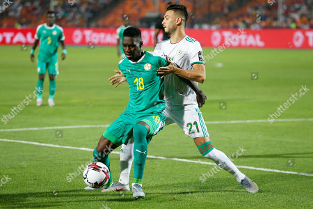 Senegal's Ismaila Sarr, front, and a21\ fight for the ball during the African Cup of Nations final soccer match between Algeria and Senegal in Cairo International stadium in Cairo, Egypt