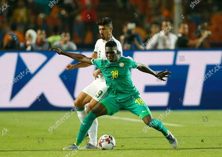 Senegal's Ismaila Sarr, front, and Algeria's Baghdad Bounedjah fight for the ball during the African Cup of Nations final soccer match between Algeria and Senegal in Cairo International stadium in Cairo, Egypt