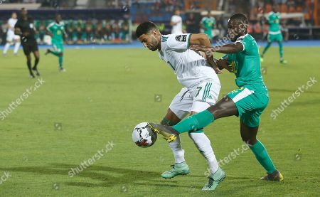 Algeria's Riyad Mahrez, left, and Senegal's Youssouf Sabaly fight for the ball during the African Cup of Nations final soccer match between Algeria and Senegal in Cairo International stadium in Cairo, Egypt