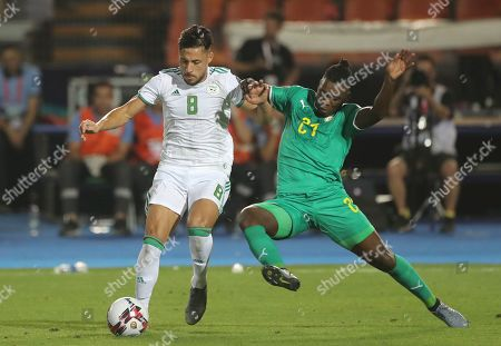 Algeria's Mohamed Belaili, left, andSenegal's Lamine Gassama fight for the ball during the African Cup of Nations final soccer match between Algeria and Senegal in Cairo International stadium in Cairo, Egypt