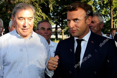 Stock Photo of French President Emmanuel Macron, right, talks with five-time Tour de France winner Belgium's Eddy Merckx during a ceremony to mark the 100th anniversary of the Tour de France yellow jersey in Pau, France