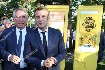 French President Emmanuel Macron, right, walks with Pau mayor Francois Bayrou during a ceremony to mark the 100th anniversary of the Tour de France yellow jersey in Pau, France