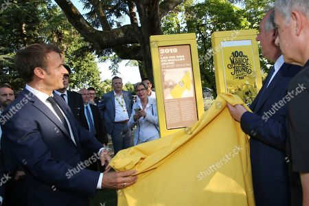 French President Emmanuel Macron, left, unveils a totem with Pau mayor Francois Bayrou during a ceremony to mark the 100th anniversary of the Tour de France yellow jersey in Pau, France