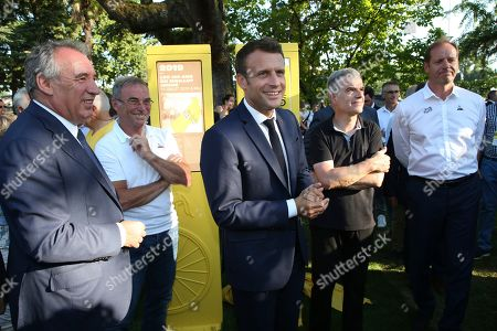 French President Emmanuel Macron, center, attends a ceremony to mark the 100th anniversary of the Tour de France yellow jersey with with Pau mayor Francois Bayrou, left, Tour de France winner France's Bernard Hinault, second left, and Tour de France director Christian Prudhomme, right, in Pau, southwestern France