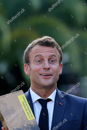 French President Emmanuel Macron gets a gift during a ceremony to mark the 100th anniversary of the Tour de France yellow jersey while Pau mayor Francois Bayrou, left, and Tour de France director Christian Prudhomme, second left, listen in Pau, France