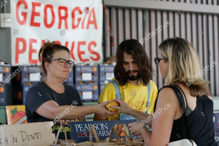 Stock Picture of On, Rebecca Kern, left, and Ryder Seigle, right, sell Pearson Farm peaches and pecans at the Ponce City Farmers Market in Atlanta
