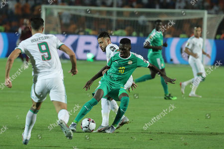 Senegal's Ismaila Sarr and Algeria's Mohamed Belaili fight for the ball during the African Cup of Nations final soccer match between Algeria and Senegal in Cairo International stadium in Cairo, Egypt