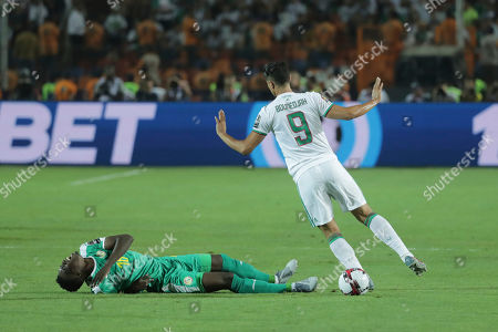Algeria's Baghdad Bounedjah,right, gestures as Senegal's Ismaila Sarr lays on the pitch during the African Cup of Nations final soccer match between Algeria and Senegal in Cairo International stadium in Cairo, Egypt