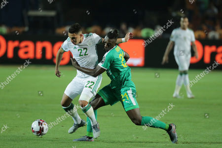Algeria's Ismael Bennacer and Senegal's Lamine Gassama fight for the ball during the African Cup of Nations final soccer match between Algeria and Senegal in Cairo International stadium in Cairo, Egypt