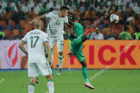 Senegal's Ismaila Sarr and Algeria's Ismael Bennacer jump for the ball during the African Cup of Nations final soccer match between Algeria and Senegal in Cairo International stadium in Cairo, Egypt