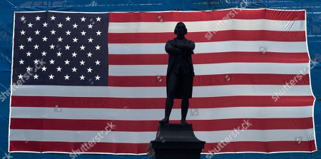 A statue of Samuel Adams is silhouetted by a large US Flag covering construction material on Faneuil Hall in Boston, Massachusetts, USA, 19 July 2019. Temperatures in the region reached 92F (33.3C) and could reach nearly 100F (37.8C) over the weekend.