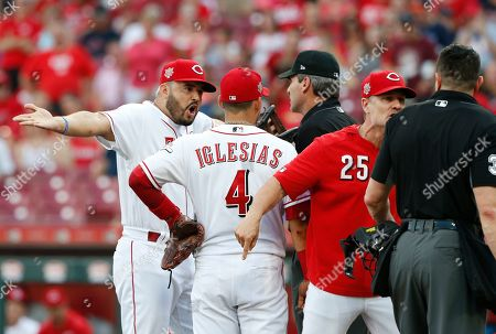 Cincinnati Reds' Eugenio Suarez, left, and Jose Iglesias (4) argue with first base umpire Angel Hernandez, rear, while Reds manager David Bell (25) argues with home plate umpire Carlos Torres, right, about called strikes during the first inning of a baseball game, in Cincinnati. Bell was ejected from the game