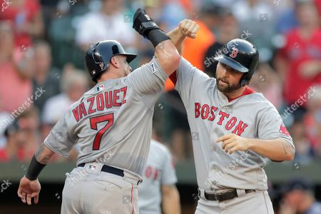 Boston Red Sox's Sam Travis, right, celebrates with Christian Vazquez after they scored on Travis' two-run home run off Baltimore Orioles starting pitcher John Means during the second inning of a baseball game, in Baltimore