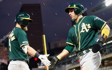 Ramon Laureano, Chris Herrmann. Oakland Athletics' Ramon Laureano, right, is greeted by Chris Herrmann after scoring the go-ahead run on a Khris Davis single off Minnesota Twins relief pitcher Ryne Harper during the sixth inning of a baseball game, in Minneapolis. The Athletics won 5-3