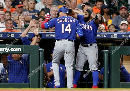 Texas Rangers' Asdrubal Cabrera (14) gets a pat on the head from Rougned Odor, right, as he heads into the dugout after his home run during the sixth inning of a baseball game against the Houston Astros, in Houston