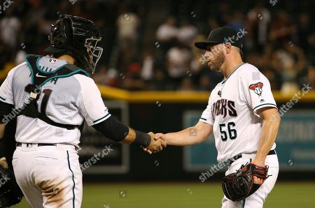 Arizona Diamondbacks relief pitcher Greg Holland (56) shakes hands with Diamondbacks catcher Alex Avila, left, celebrating the final out in the ninth inning of a baseball game against the Milwaukee Brewers, in Phoenix. The Diamondbacks defeated the Brewers 10-7