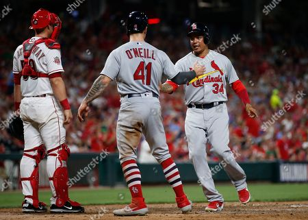 Tyler O'Neill, Yairo Munoz. St. Louis Cardinals' Tyler O'Neill (41) and Yairo Munoz (34) celebrate after scoring on a double off the bat of Paul DeJong (12) during the sixth inning of a baseball game against the Cincinnati Reds, in Cincinnati. At left is Reds' Ryan Lavarnway