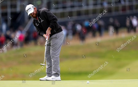 J. B. Holmes attempts a putt on the first green