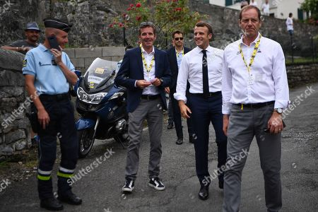 French President Emmanuel Macron (2ndR) walks with Tour de France director Christian Prudhomme (R) on the route of the fourteenth stage of the 106th edition of the Tour de France cycling race between Tarbes and Tourmalet Bareges, on July 20, 2019.