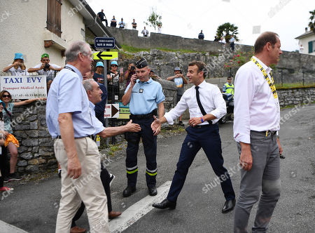 French President Emmanuel Macron (2ndR) shakes hands with guests past Tour de France director Christian Prudhomme (R) on the route of the fourteenth stage of the 106th edition of the Tour de France cycling race between Tarbes and Tourmalet Bareges, on July 20, 2019.