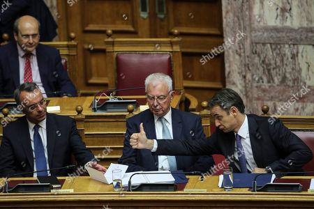 Kyriakos Mitsotakis, Christos Staikouras, Panagiotis Pikrammenos. Greece's Prime Minister Kyriakos Mitsotakis, right, gives a thump up to Greek Finance Minister Christos Staikouras, left, as Deputy Prime Minister Panagiotis Pikrammenos, center, looks on during a parliamentary session in Athens, on