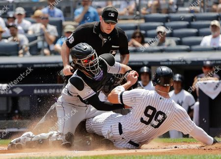 Colorado Rockies catcher Tony Wolters, left, tags out New York Yankees' Aaron Judge, right, during the first inning of a baseball game as home plate umpire Chris Conroy watches, in New York