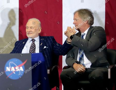 Buzz Aldrin, Mike Pence, Rick Armstrong. Apollo 11 astronaut Buzz Aldrin, left, clasps hands with Rick Armstrong, son of Apollo 11 astronaut Neil Armstrong as they are introduced at an event at the Kennedy Space Center for the anniversary of the moon landing, in Cape Canaveral, Fla