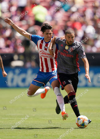 Benfica midfielder Adel Taarabt, right, is held from behind by Chivas midfielder Alan Cervantes during the second half of an International Champions Cup soccer match, in Santa Clara, Calif. Benfica won 3-0