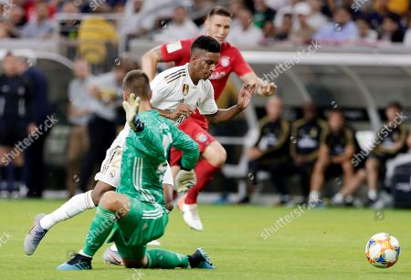 Real Madrid forward Rodrygo Goes, center, is tripped by FC Bayern goalkeeper Sven Ulreich, left, as he tries to score and Niklas Süle, back, looks on during the second half of an International Champions Cup soccer match, in Houston. Ulreich received a red card for a professional foul on the play