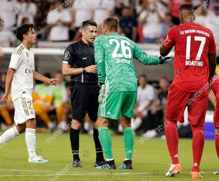 FC Bayern goalkeeper Sven Ulreich (26) argues with referee Ramy Touchan after getting a red card for tripping Real Madrid forward Rodrygo Goes, between Dani Carvajal (2) and Jerome Boateng (17) during the second half of an International Champions Cup soccer match, in Houston